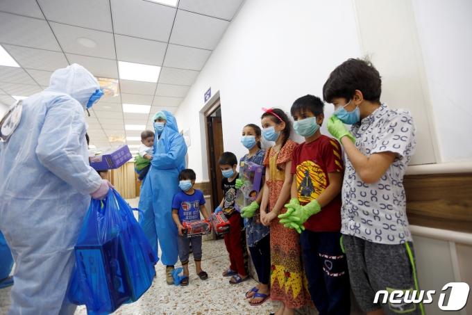 이라크 나자프의 한 코로나19 격리병동에서 2020년 4월 15일 간호사와 자원봉사자들이 방호복을 입고 아이들에게 선물을 주는 모습.  © 로이터=뉴스1