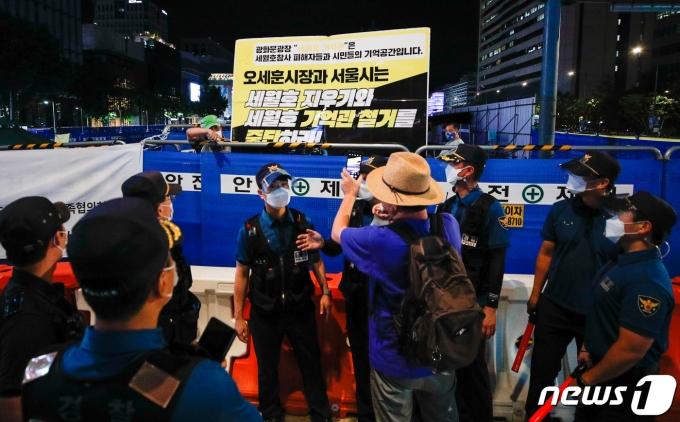26일 저녁 서울 종로구 광화문 광장에서 한 시민이 마스크를 벗은 채 세월호 기억공간 쪽을 스마트폰으로 촬영하고 있다. 2021.7.26/뉴스1 © News1 안은나 기자