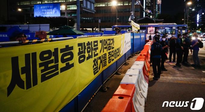 26일 저녁 서울 종로구 광화문 광장에서 한 시민이 마스크를 벗은 채 세월호 기억공간 쪽을 스마트폰으로 촬영하며 언성을 높이자 경찰들이 이를 저지하고 있다. 2021.7.26/뉴스1 © News1 안은나 기자
