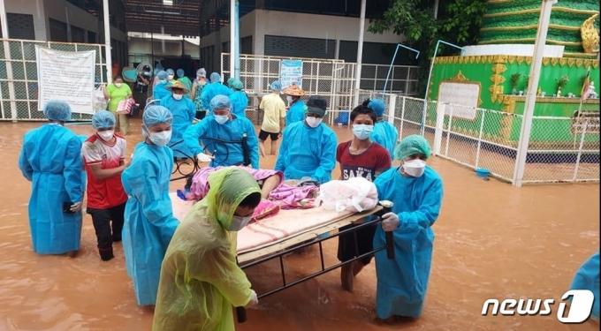 미얀마에서 홍수가 발생해 의료진들이 코로나19 환자를 침대에 누인채 이동시키고 있다.(카렌공보센터 페이스북 갈무리)© 뉴스1