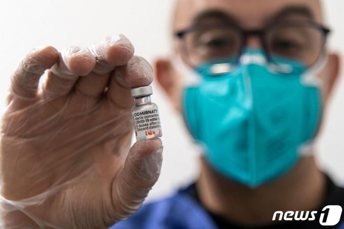 이탈리아 토리노의 백신 접종소에서 2021년 4월 14일 한 의료진이 화이자 백신 바이알을 선보이고 있다. © AFP=뉴스1