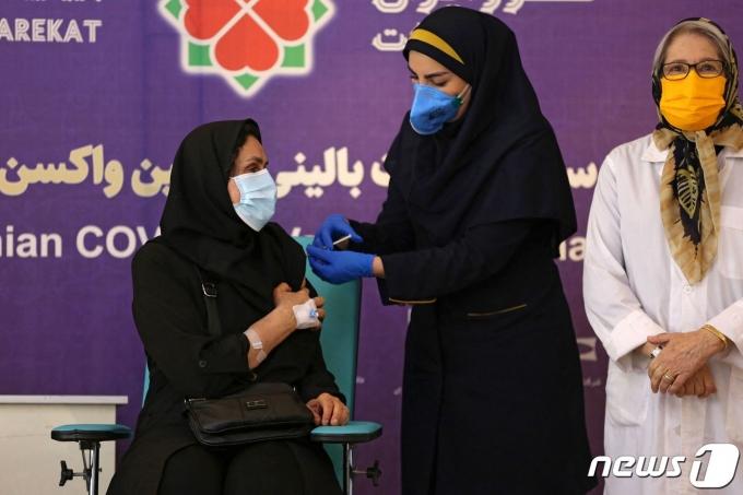 이란 수도 테헤란에서 2021년 3월 15일 의료진에게 이란이 자체 개발한 코로나19 백신을 접종하는 모습.  © AFP=뉴스1