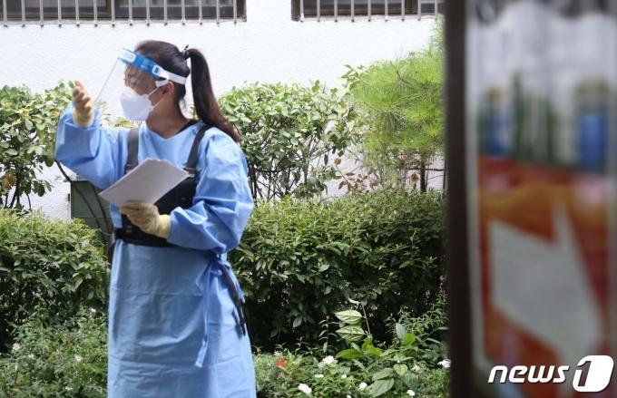 연일 폭염이 계속되는 28일 서울 광진구보건소 선별진료소에서 의료진이 얼음조끼를 입은 채 시민들을 안내하고 있다. 2021.7.28/뉴스1 © News1 구진욱 기자