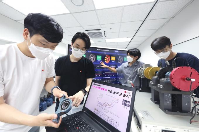 원프레딕트 관계자들이 시험 설비에 꾸려진 로봇설비와 베어링 부품을 AI 예지 보전 솔루션을 통해 진단하는 모습. /사진제공=LGU+