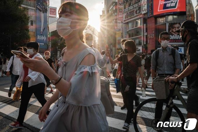 28일 마스크를 쓴 행인들이 도쿄 시내의 횡단보도를 건너고 있다. © AFP=뉴스1