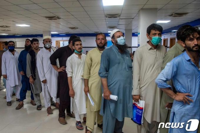6일(현지시간) 파키스탄 페샤와르에 있는 코로나19 백신 접종 센터에서 중동 지역으로 갈 해외 근로자들이 모더나 백신을 맞기 위해 줄을 서 있다. © AFP=뉴스1 © News1 우동명 기자