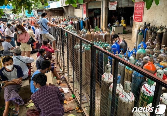 11일(현지시간) 코로나19 확진자 급증으로 산소통 부족 사태를 겪고있는 미얀마 양곤의 공장 밖에서 시민들이 산소통의 충전을 기다리고 있다. © AFP=뉴스1 © News1 우동명 기자