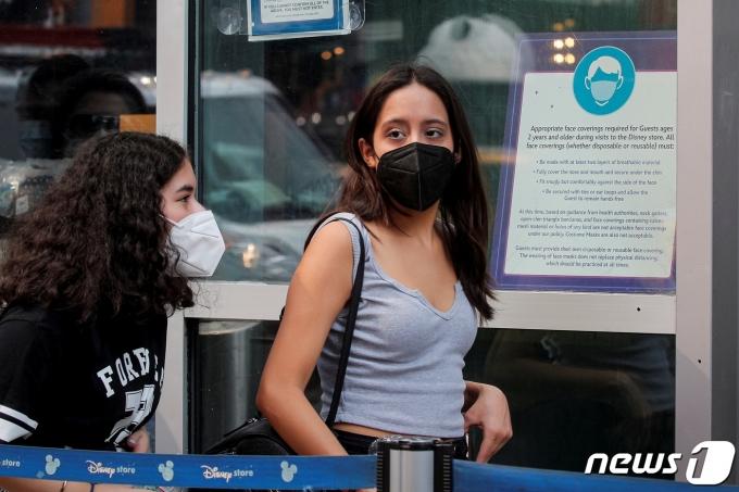 미국 질병통제예방센터(CDC)가 백신 접종자에게도 다시 실내 마스크 착용을 권고하자 마스크를 쓰는 사람들이 늘고 있다. 사진은 CCD 발표가 있던 날인 2021년 7월 27일(현지시간) 뉴욕 타임스퀘어의 디즈니 스토어에 들어가는 사람들이 마스크를 쓴 모습. © 로이터=뉴스1 © News1 최서윤 기자
