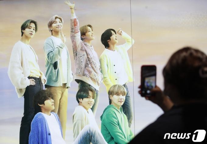 7일 오후 서울 중구 롯데면세점에 마련된 BTS의 광고판 앞에서 한 시민이 핸드폰에 방탄소년단의 모습을 담고 있다. 2021.7.7/뉴스1 © News1 권현진 기자