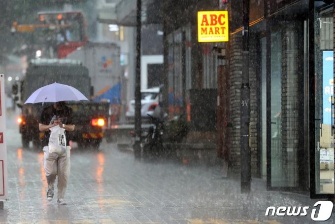 서울지역에 국지성 폭우가 내린 19일 오후 서울 중구 명동거리에서 우산을 쓴 시민이 발걸음을 재촉하고 있다. 2021.7.19/뉴스1 © News1 황기선 기자