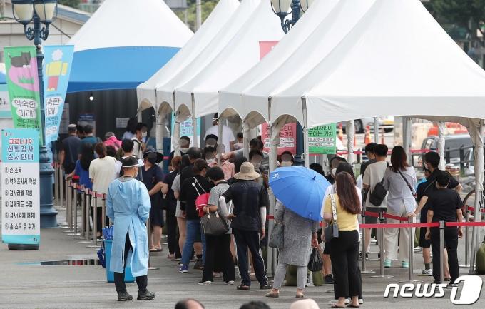 서울 중구 서울역 광장에 마련된 코로나19 임시선별검사소를 찾은 시민들이 길게 줄지어 대기하고 있다./뉴스1 © News1 박정호 기자