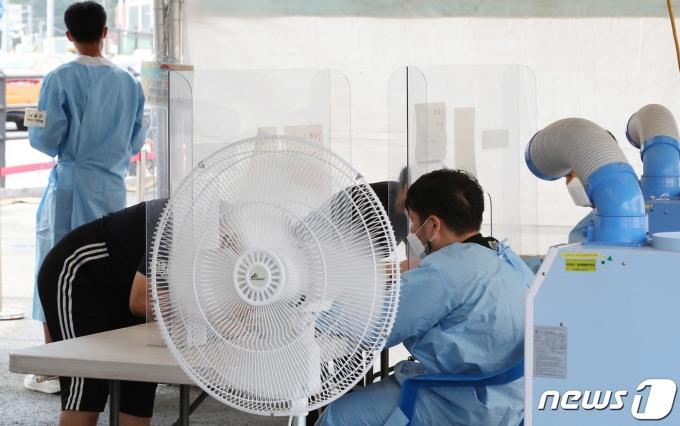 무더위가 계속되고 있는 31일 오전 서울 중구 서울역 광장에 마련된 코로나19 임시선별검사소에 선풍기와 냉풍기가 돌아가고 있다. /뉴스1 © News1 박정호 기자