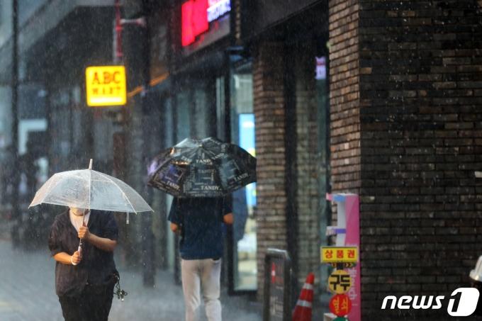 서울지역에 국지성 폭우가 내린 19일 오후 명동 거리에서 우산 쓴 시민이 발걸음을 재촉하고 있다. 2021.7.19/뉴스1 © News1 황기선 기자
