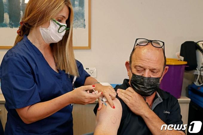 12일(현지시간) 이스라엘 텔아비브의 셰바 메디컬 센터에서 시민이 코로나19 화이자 백신을 세계서 처음으로 3번째 접종을 받고 있다. © AFP=뉴스1 © News1 우동명 기자