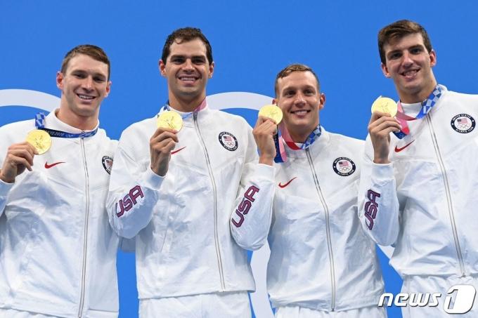 케일럽 드레셀(오른쪽에서 2번째)이 2020 도쿄 올림픽 남자 혼계영 400m 시상식에서 금메달을 들고 동료들과 기뻐하고 있다. © AFP=뉴스1