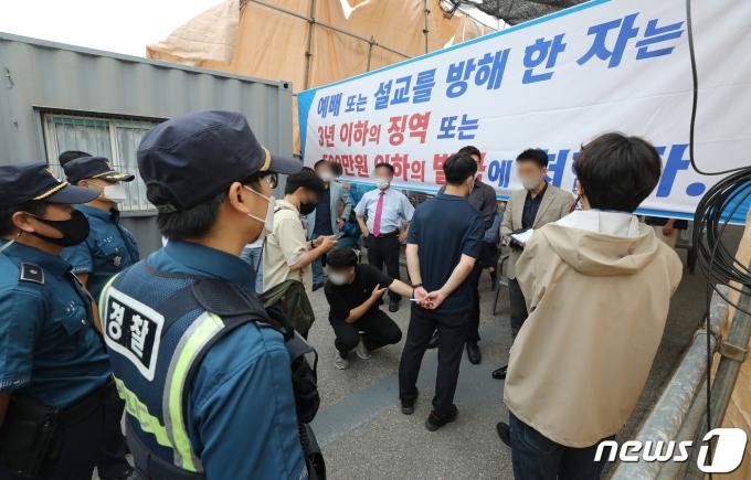 1일 오전 서울 성북구 사랑제일교회 앞에서 경찰이 교회 관계자들과 대면예배 중단과 관련해 이야기하고 있다. 2021.8.1/뉴스1 © News1 임세영 기자