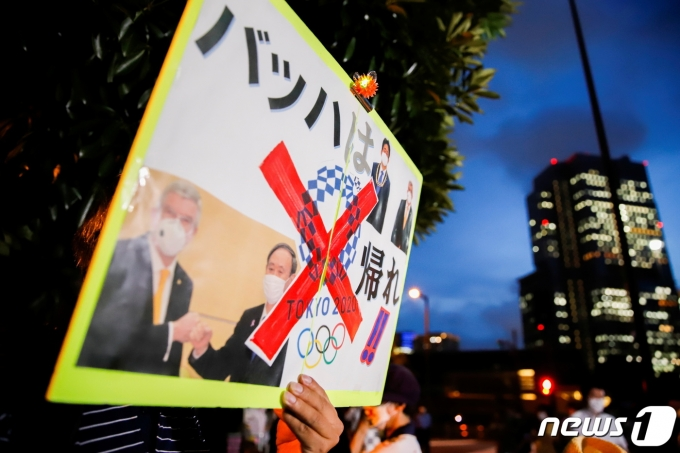 29일(현지시간) 일본에서 코로나19 신규 확진자가 연일 최다 발생하자 도쿄 올림픽 취소를 요구하는 시위가 스가 요시히데 일본 총리 집무실 앞에서 열렸다. 29일(현지시간) 기준 일본 내 코로나19 확진자는 사상 처음으로 1만명을 돌파했다. © 로이터=뉴스1 © News1 이정후 기자