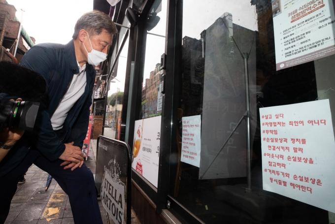 국민의힘 대권주자인 최재형 전 감사원장이 1일 오후 서울 용산구 이태원 세계음식거리에서 휴업한 가게에 붙어있는 문구를 읽고있다. 2021.8.1/뉴스1 © News1 국회사진취재단