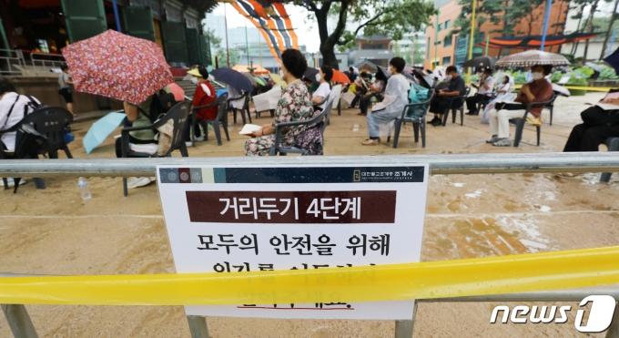 사회적 거리두기 4단계 방역지침이 2주 연기된 뒤 두 번째 일요일인 1일 서울 종로구 조계사 대웅전 앞 마당에서 불자들이 기도를 하고 있다. 2021.8.1/뉴스1 © News1 박지혜 기자