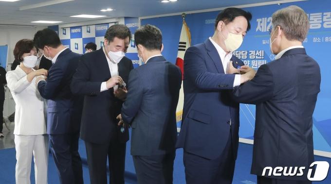 더불어민주당 대선 예비후보들이 28일 오전 서울 여의도 중앙당사에서 열린 제20대 대선 후보자 '원팀'협약식에서  김두관 의원(오른쪽 두번째)과 이재명 경기도지사(오른쪽 첫번째)가 배지를 서로에게 달아주고 있다.  2021.7.28/뉴스1 © News1 이동해 기자