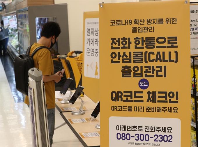 2일 서울시에 따르면 신종 코로나바이러스 감염증(코로나19) 확산세를 꺾기 위해 대중교통 운영 추가 감축과 대헝점포 영업 제한이 검토되고 있다. 사진은 지난달 30일 서울의 한 대형마트에서 QR코드 체크를 하는 시민 모습. /사진=뉴스1