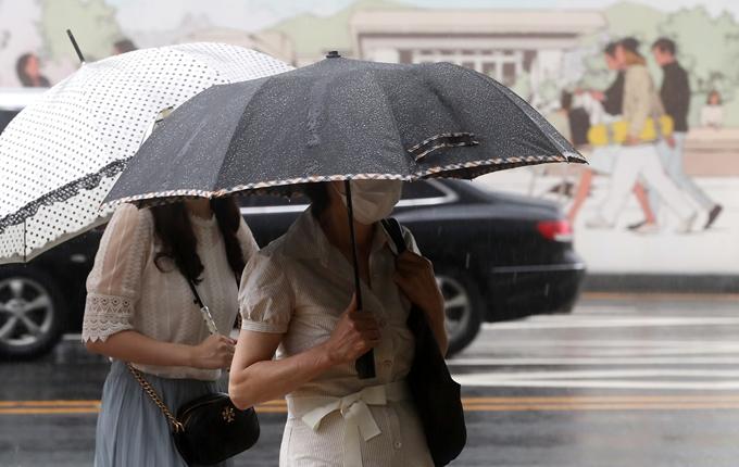 오는 3일은 전국 대부분 지역에 33도 안팎의 무더위가 이어지는 가운데 소나기가 내릴 전망이다. 사진은 2일 서울 종로구 광화문네거리에서 우산을 쓴 채 출근하는 시민 모습. /사진=뉴스1