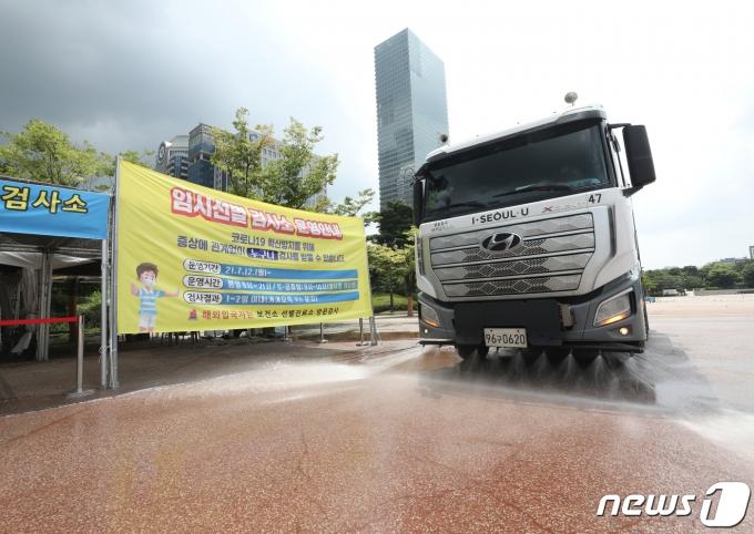 3일 서울 여의도공원에 마련된 임시선별진료소에서 살수차가 열기를 식히기 위해 도로에 물을 뿌리고 있다. 2021.8.3/뉴스1 © News1 신웅수 기자