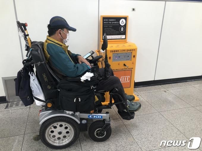 전동휠체어 급속충전소에서 휠체어 배터리를 충전하는 김종호씨(가명).© 뉴스1 금준혁 기자