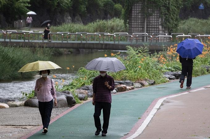오는 5일 전국 곳곳에 천둥·번개를 동반한 소나기가 내리는 가운데 낮 최고기온이 34도 안팎까지 오르는 등 무더위가 나타날 전망이다. 사진은 지난달 4일 서울 서대문구 홍제천에서 우산을 쓴 채 이동하는 시민 모습. /사진=뉴스1