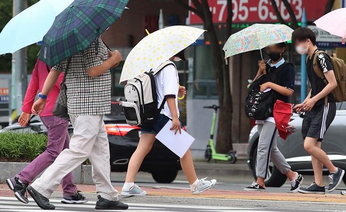 5일은 전국 곳곳에 천둥·번개를 동반한 소나기가 내리는 가운데 낮 최고기온이 34도 안팎까지 오르겠다. 사진은 지난달 5일 대구 도심 횡산보도에서 우산을 쓴 채 이동하는 시민 모습. /사진=뉴스1