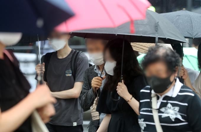 오는 6일은 낮 최고기온이 35도 안팎까지 오르는 등 무더운 날씨일 전망이다. 내륙 곳곳에는 소나기가 내릴 것으로 보인다. 사진은 지난 2일 서울 종로구 광화문네거리에서 우산을 쓴 채 이동하는 시민 모습. /사진=뉴스1
