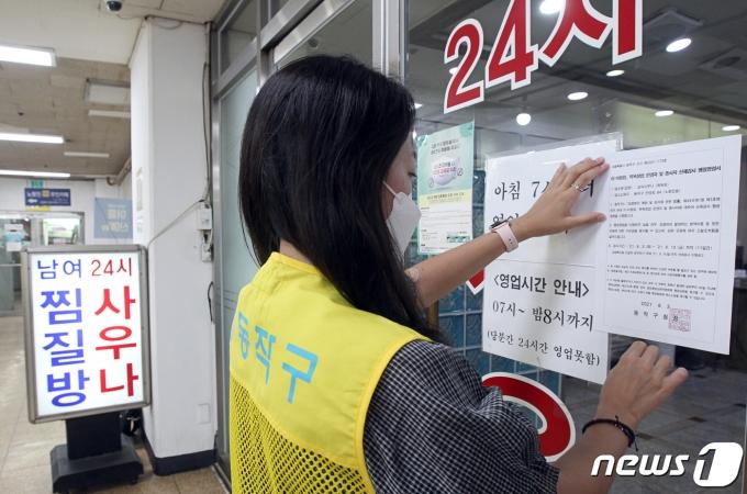 4일 동작구청 관계자가 서울 노량진동 한 사우나 업소에서 코로나19 진단검사 행정명령서를 출입문에 부착하고 있다.(동작구 제공)2021.8.4/뉴스1