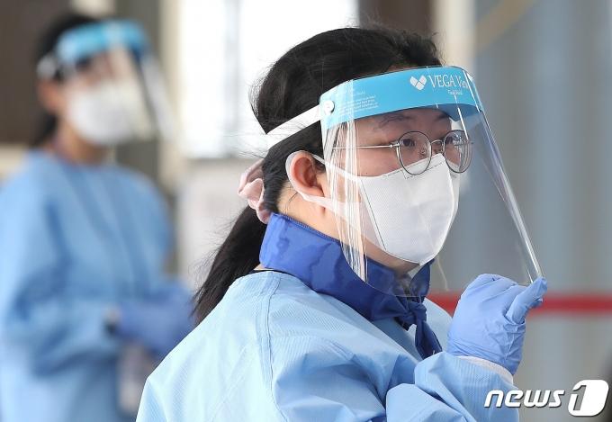 5일 오전 서울 중구 서울역광장에 마련된 신종 코로나바이러스 감염증(코로나19) 임시선별진료소에서 한 의료진이 아이스 스카프로 더위를 식히고 있다. 2021.8.5/뉴스1 © News1 임세영 기자