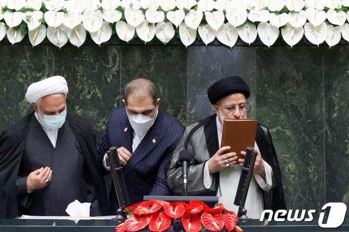 에브라힘 라이시 이란 신임 대통령이 2021년 8월 5일 의회에서 가진 취임식에서 취임 선서 후 이슬람 경전 코란에 입을 맞추고 있다. © 로이터=뉴스1 © News1 최서윤 기자
