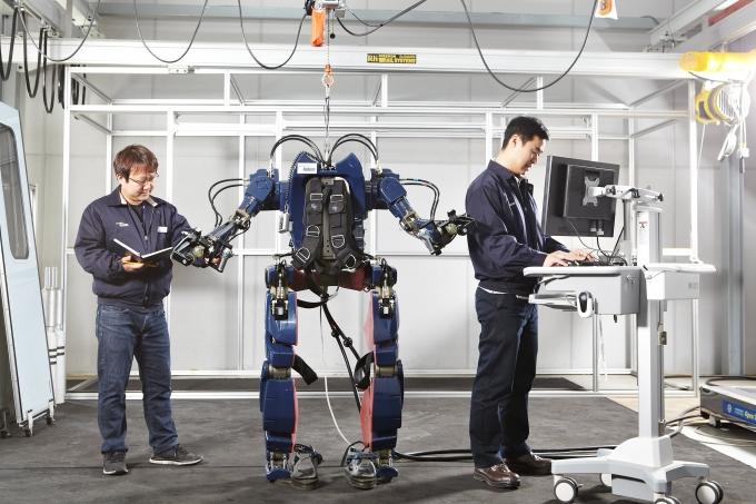 현대로템 연구원들이 웨어러블 로봇을 살피고 있다. / 사진=현대로템