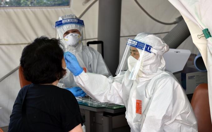 신종 코로나바이러스 감염증(코로나19) 신규 확진자가 22일 0시 기준 1619명을 기록했다. 사진은 대구 달서구 보건소 선별진료소에서 의료진이 검체 채취를 하고 있는 모습./사진=뉴시스