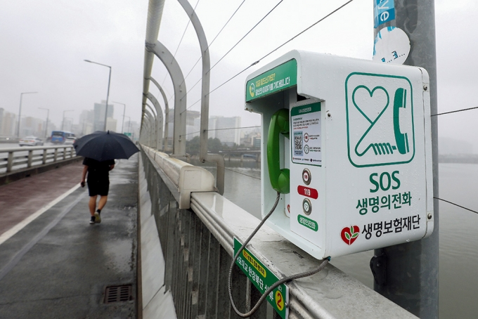 지난 7월 서울 마포대교에서 자살 예방을 위해 설치된 '생명의 전화'를 한 시민이 지나는 모습. /사진=뉴스1 DB