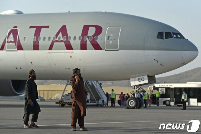 미국인 등 승객 200명이 지난 9일(현지시간) 아프가니스탄 카불 공항에서 카타르 항공기에 오르는 동안 탈레반 조직원들이 경비를 서고 있다. 지난달 30일 밤 11시59분 마지막 미 군 수송기가 떠난 이후 첫 탈출 비행이다. © AFP=뉴스1 © News1 안은나 기자