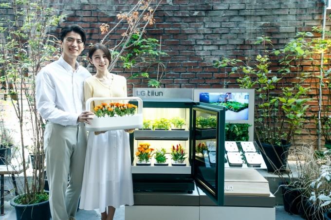 서울 성수동에 위치한 복합문화공간 '플라츠'에 15일부터 11월 초까지 운영하는 신개념 식물생활가전 'LG 틔운' 팝업스토어인 '틔운 하우스'에서 모델들이 LG 틔운과 LG 틔운 미니를 체험하고 있다. / 사진=LG전자